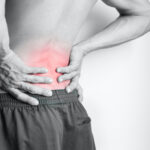 Athletic man's back pain isolated in black and white